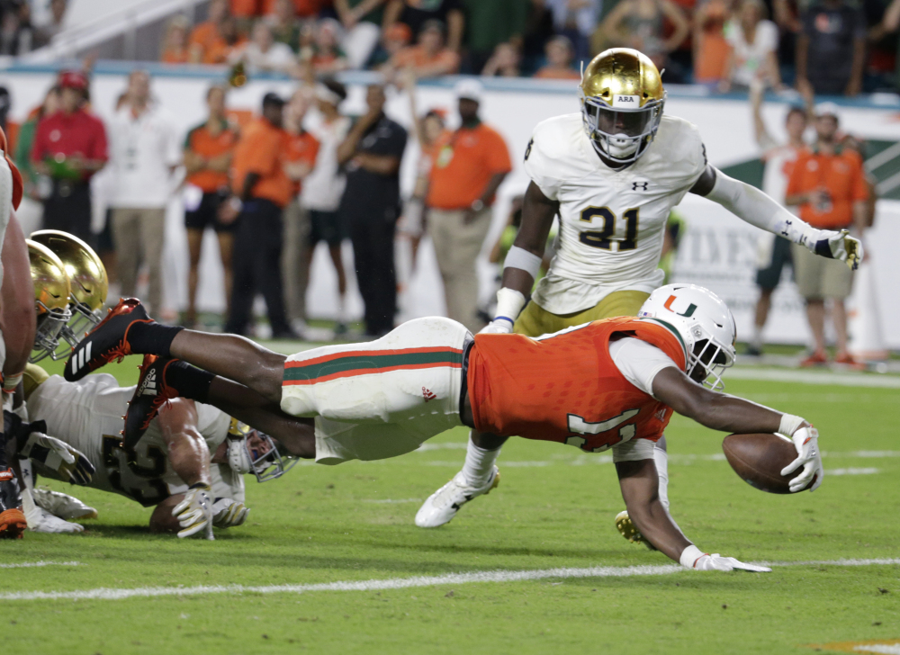 Miami's DeeJay Dallas scores a touchdown past Notre Dame safety Jalen Elliott during the second half Saturday night in Miami Gardens, Fla. Miami won 41-8.