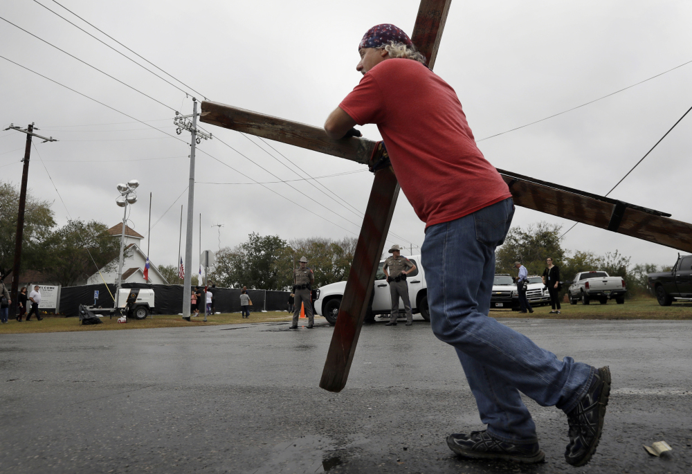 Stephen Hope carries a cross past the Sutherland Springs First Baptist Church in Texas after services held at a temporary site on Sunday, a week after 26 people were killed in the church.