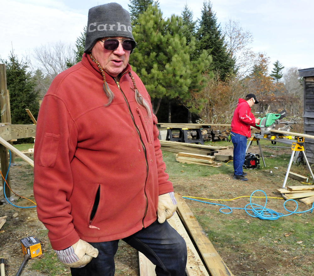 Phil White Hawk talks about the new wheelchair ramp under construction at the Palermo Community Center on Sunday. At right, Brian Taylor cuts wood for the project.