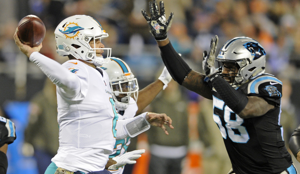 Miami's Jay Cutler tries to get off a pass while Carolina's Thomas Davis closes in during the first half of their game Monday night in Charlotte, North Carolina. Carolina led, 45-14, midway through the fourth quarter.
