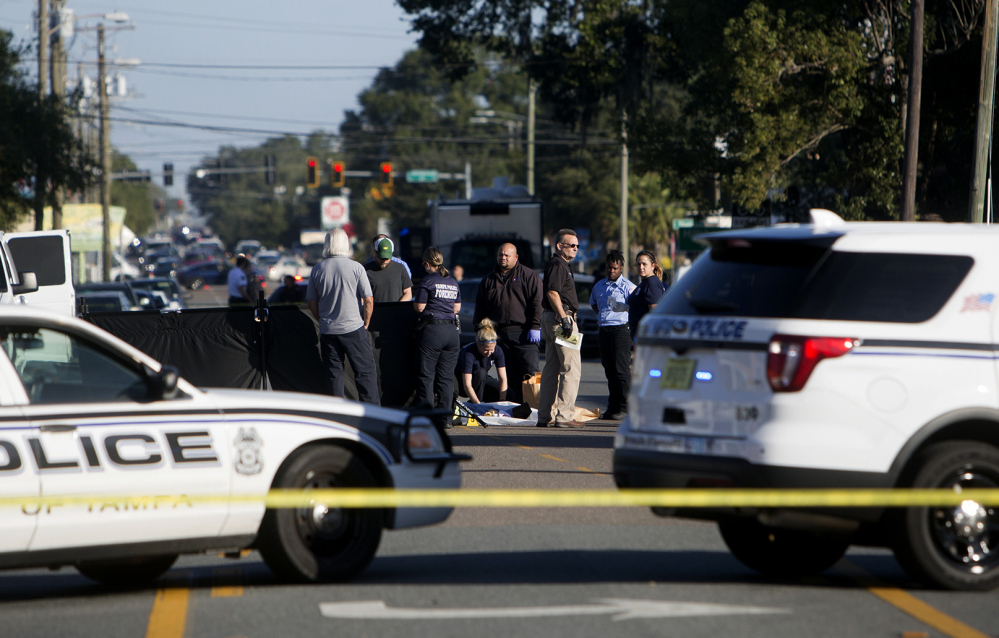 Law enforcement agents investigate a fatal shooting in the Seminole Heights neighborhood in Tampa, Fla., on Tuesday.  Police searched the neighborhood after a person was shot dead, possibly by a serial killer.