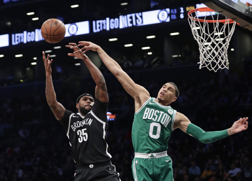 Boston's Jayson Tatum blocks a shot by Brooklyn's Trevor Booker during the Celtics' 109-102 win Tuesday in New York.