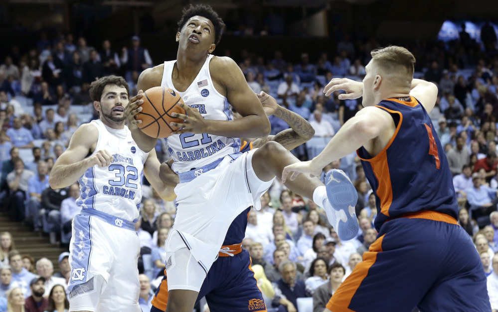 Sterling Manley of North Carolina collects a rebound in front of teammate Luke Maye as Nate Sestina of Bucknell moves in Wednesday night during the first half of North Carolina's 93-81 victory.