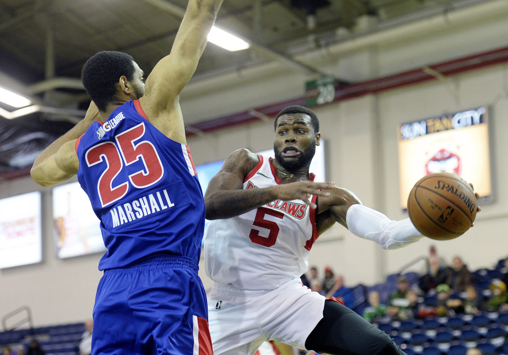 Kadeem Allen of the Red Claws passes the ball against Zeke Marshall of the Grand Rapids Drive during Maine's 99-96 win Thursday night at the Expo.