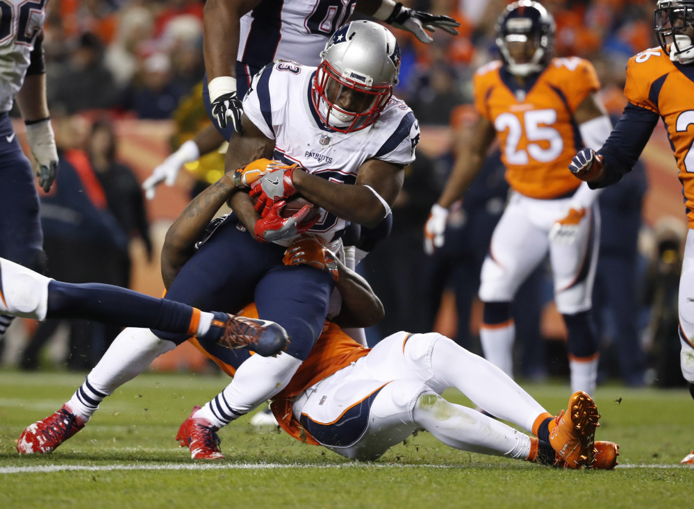 Dion Lewis breaks free of Denver strong safety Justin Simmons en route to a touchdown in the Patriots' 41-16 victory over the Broncos on Nov 16, 2017.