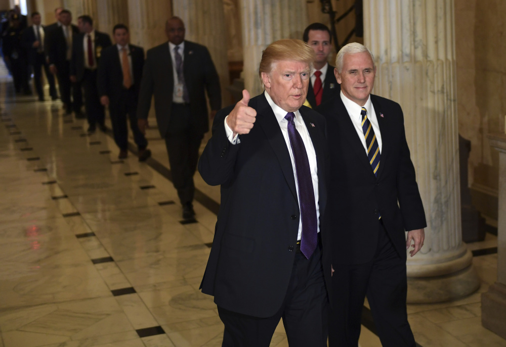 President Trump gives a thumbs up as he walks with Vice President Mike Pence as he departs Capitol Hill in Washington on Thursday. Across the Capitol, Democrats pointed to new numbers Friday showing the Senate version of the Republican tax plan would boost taxes on lower- and middle-income Americans.