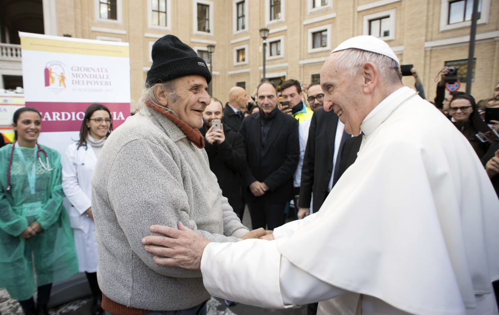 L'Osservatore Romano via AP Pope Francis greets an unidentified man during a surprise visit to a small facility near St. Peter's Square where doctors on a volunteer basis give poor people medical exams, Thursday. Francis decried that, increasingly, only the privileged can afford sophisticated medical treatments and urged lawmakers to ensure that health care laws protect the