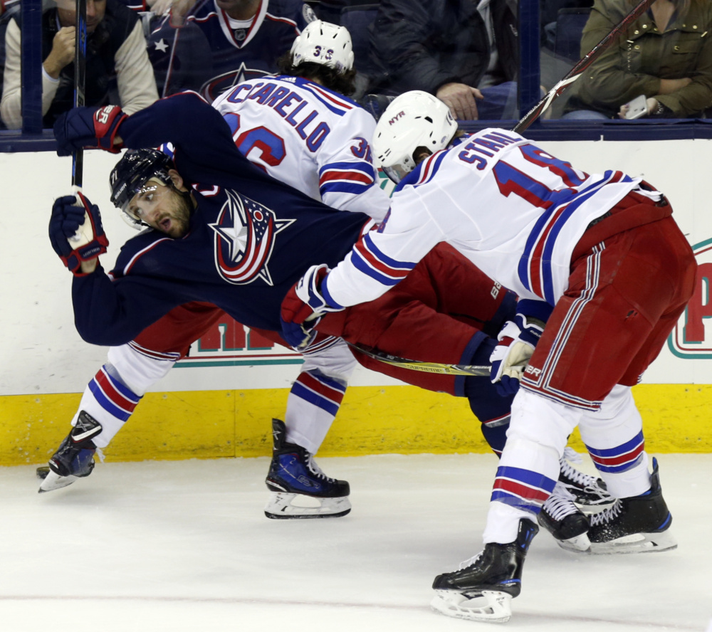 Rangers defenseman Marc Staal, right, checks Columbus' Nick Foligno, left, behind Rangers forward Mats Zuccarello in the third period Friday night in Columbus, Ohio.