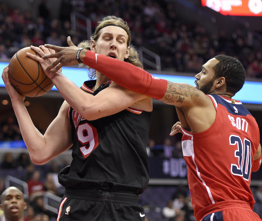 Kelly Olynyk of the Miami Heat attempts to keep the ball from Mike Scott of the Washington Wizards during the first half of the Heat's 91-88 victory Friday night at Washington. Miami saw a 25-point lead go down to one before holding on.