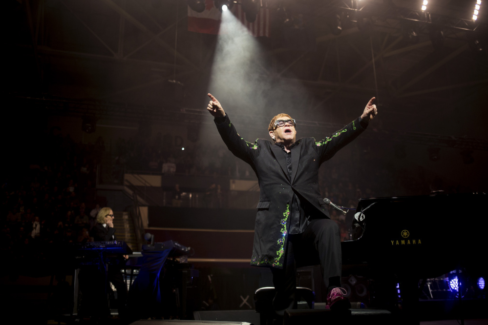 Elton John leaves the piano and gestures to the excited crowd during his first song Friday at the Cross Insurance Arena.