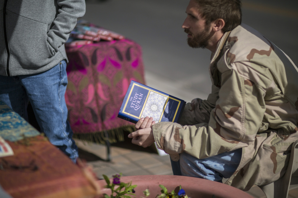 Zack Kershaw, a visitor to the Islamic Center's table, holds a Koran.