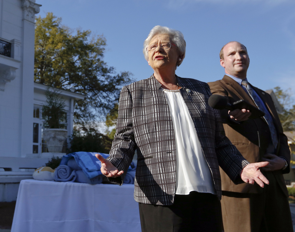 Alabama Gov. Kay Ivey speaks to the media Friday in Montgomery. Ivey said she plans to vote for Roy Moore.