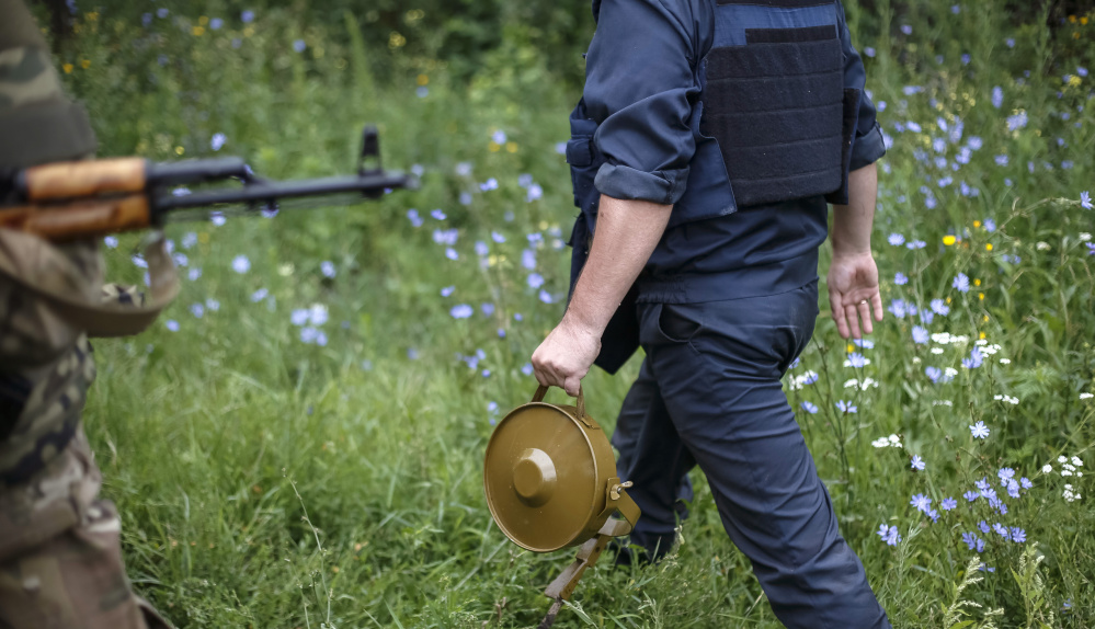 A military demolitions expert, or sapper, holds a land mine  in the eastern Ukrainian village of Semenovka in 2014.