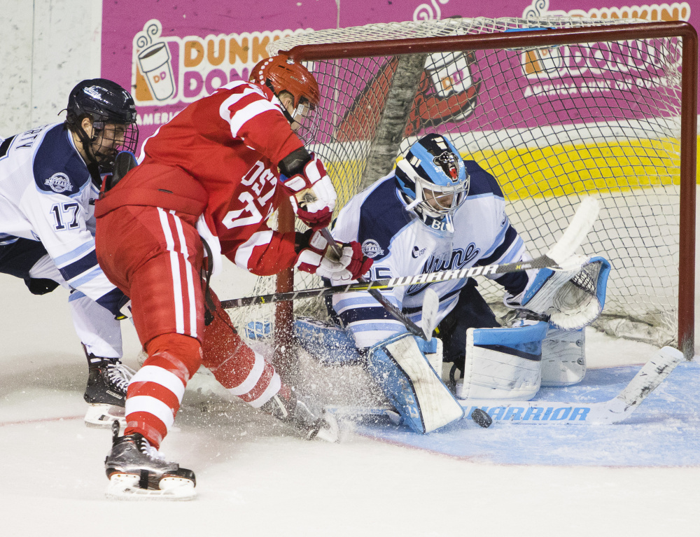 Maine goalie Rob McGovern gets a stick in front of a shot by Brady Tkachuk of Boston University as Maine defenseman Dante Fabro closes in Saturday night during BU's 7-0 victory at Cross Insurance Arena.