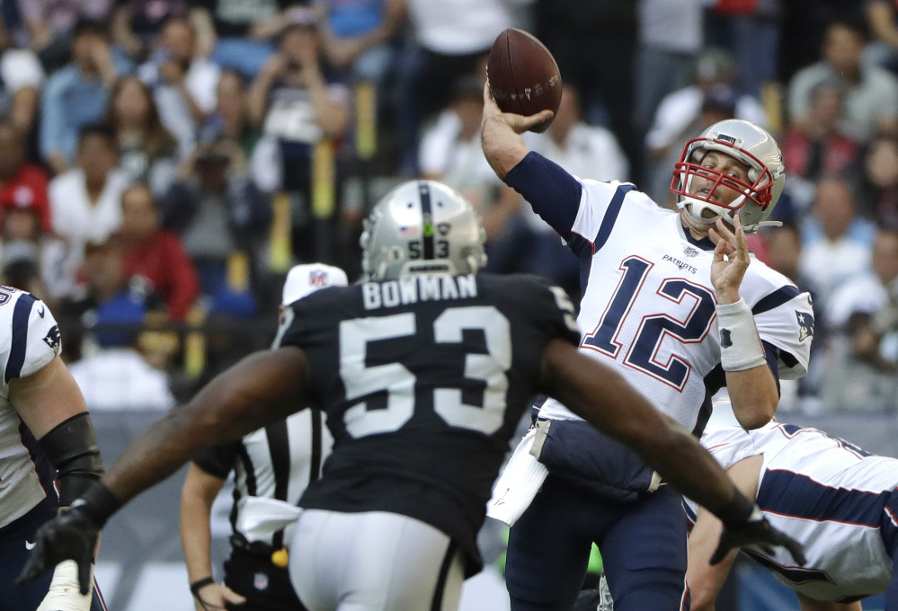 Patriots quarterback Tom Brady releases a pass under pressure from Raiders linebacker NaVorro Bowman. Brady went over the 300-yard mark for the sixth time this season, leading New England to a 33-8 win in Mexico City.