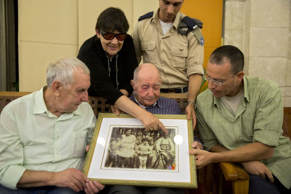 Israeli Holocaust survivor Eliahu Pietruszka, center, looks at a picture with Alexandre Pietruszka and family in the central Israeli city of Kfar Saba. Pietruszka who fled Poland at the beginning of World War II and thought his entire family had perished learned that a younger brother had also survived, and his son, 66-year-old Alexandre, flew from Russia to see him.