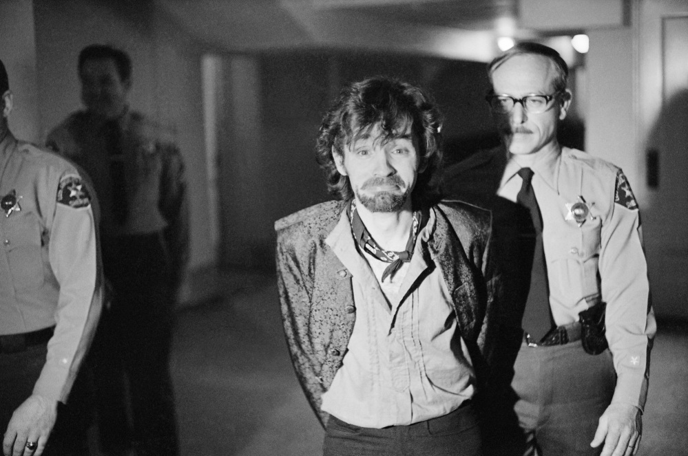 Charles Manson reacts to photographers as he goes to lunch after an outbreak in court that resulted in his ejection in 1970, along with three female co-defendants, during the Sharon Tate murder trial. Authorities say Manson, cult leader and mastermind behind 1969 deaths of Tate and several others, died on Sunday. He was 83.