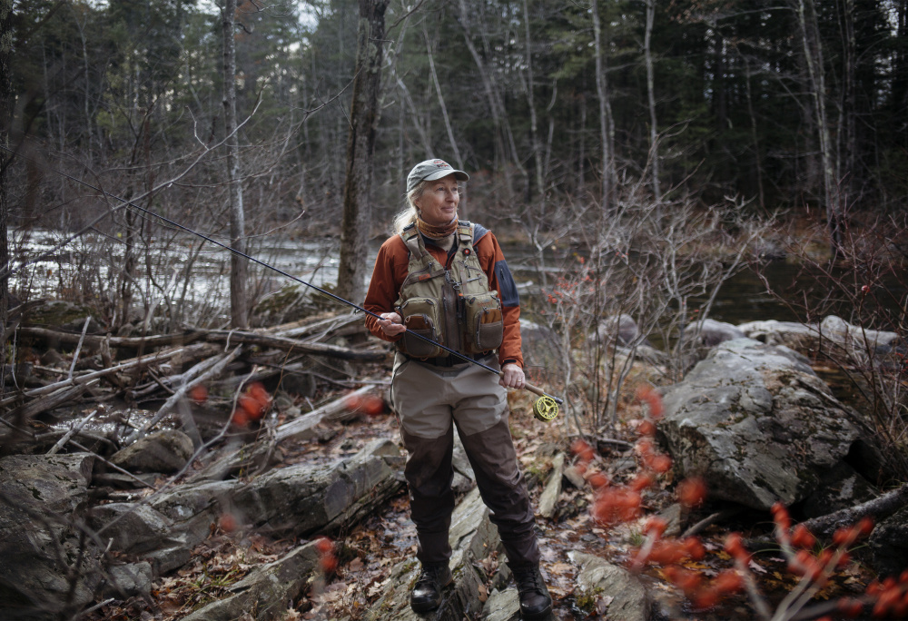"Evelyn King stands near the bank of the Prescumpscot River in Windham. King is the founder of the Maine Women Fly Fishers and is a big advocate for getting more women out in nature. ""For me it's sharing that passion. I love the time I'm on the water and I want to help other people experience that,"" King said."