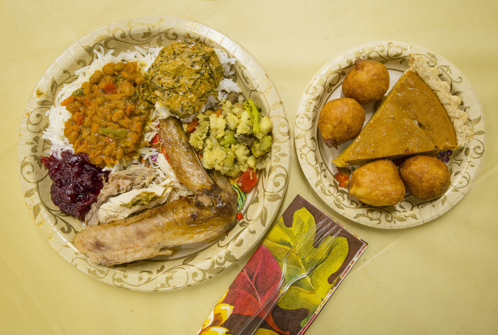 For many Mainers, Thanksgiving is a chance to blend cultures and cuisines. On the small plate are pumpkin pie and African doughnuts. On the large plate are, clockwise from top, Congolese fumbwa, stuffing, traditional Thanksgiving turkey, cranberry sauce and South African chakalaka.
