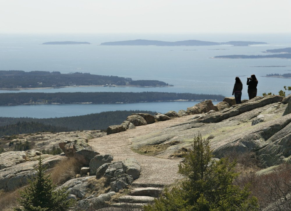 Two women take in the view from Cadillac Mountain in Acadia National Park. A proposed 180 percent jump for vehicle passes caught many people by surprise.