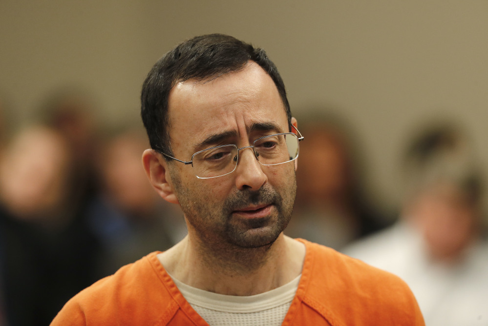Larry Nassar appears in court for his plea hearing Wednesday in Lansing, Mich. Nasser, a former sports doctor accused of molesting girls while working for USA Gymnastics and Michigan State University, pleaded guilty to multiple charges of sexual assault and faces at least 25 years in prison.