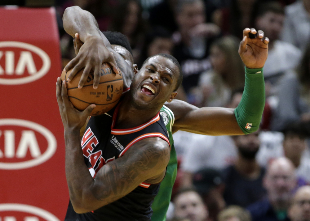 Miami's Dion Waiters fights for the ball with Boston's Jaylen Brown in the first half Wednesday in Miami.