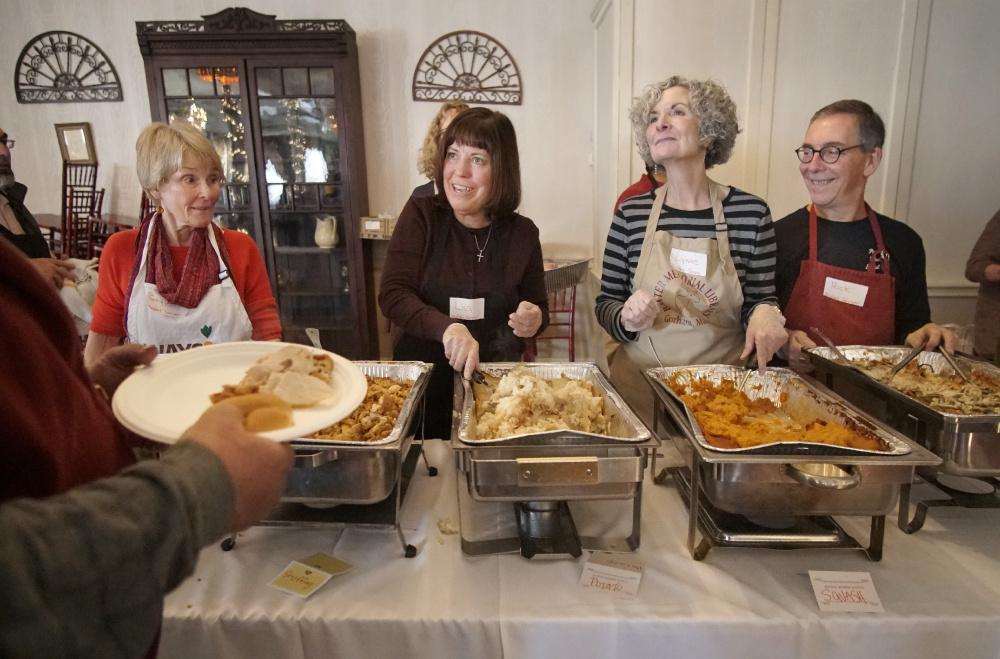 Volunteer Lisa Reardon, second from left, serves up mashed potatoes to an attendee at the Portland Club on Thursday. Joining her on the serving line are Gayle Duncan, left, and Lynne and Rick Gammon, right. About 50 volunteers helped to serve about 250 meals.