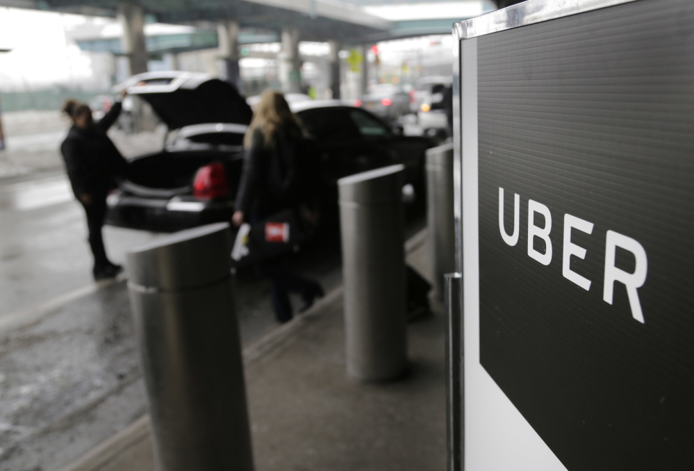 A sign marks a pick-up point for Uber service at LaGuardia Airport in New York. The ride-hailing company paid hackers $100,000 to delete stolen data about customers and drivers and to keep quiet about the breach.