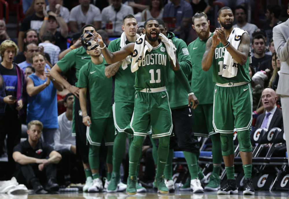 Kyrie Irving of the Celtics watches with teammates during the second half of their loss to the Heat in Miami on Wednesday night. Irving says scoring achievements can't compare to being on an 'unbelievable team.'