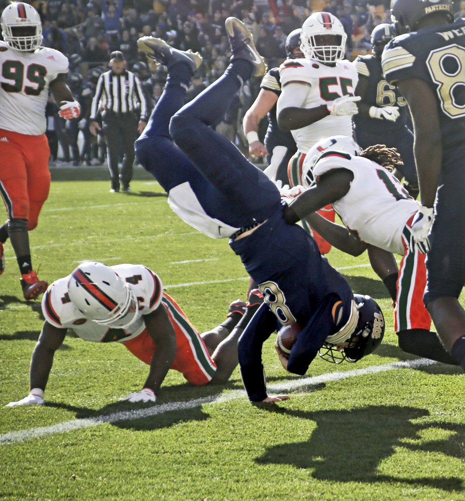 Pitt quarterback Kenny Pickett flips over defensive back Jaquan Johnson during the first half of the Panthers' 24-14 win over Miami in Pittsburgh on Friday. (AP Photo/Keith Srakocic)