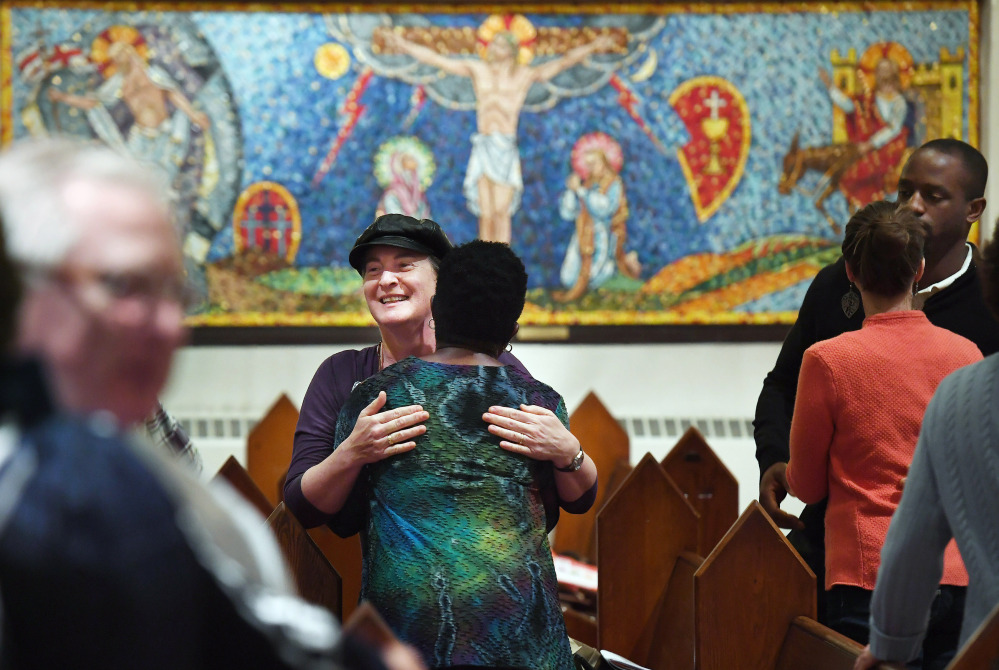 "Isabelle Melese-d'Hospital, facing the camera, embraces Charleen Ward during a service at St. Margaret's Episcopal Church in Washington, D.C. ""I needed to have that family support of the church"" after the 2016 election, Ward said."