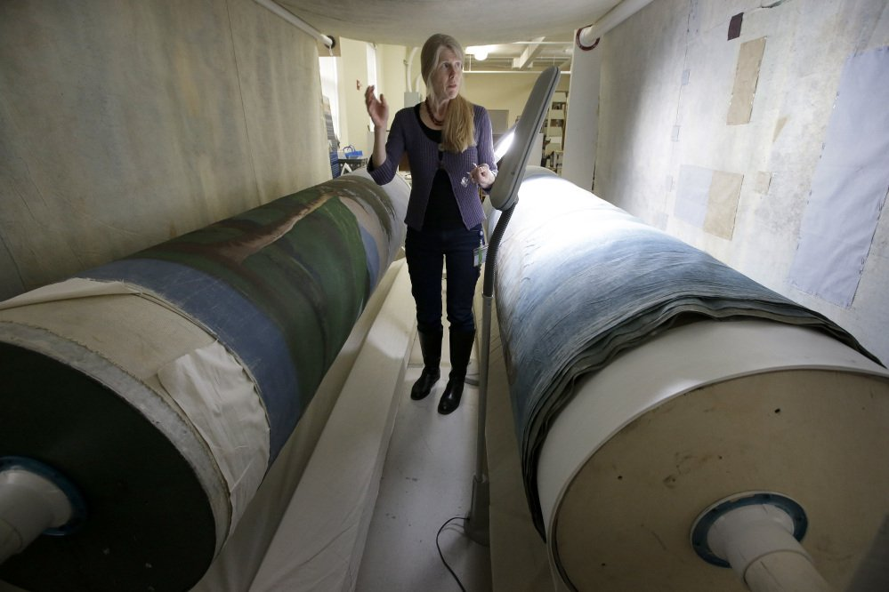 "Textile conservator Kate Tarleton of Rochester, Mass., stands between two oversized spools holding part of the ""Grand Panorama of a Whaling Voyage Round the World,"" at the New Bedford Whaling Museum in Massachusetts."