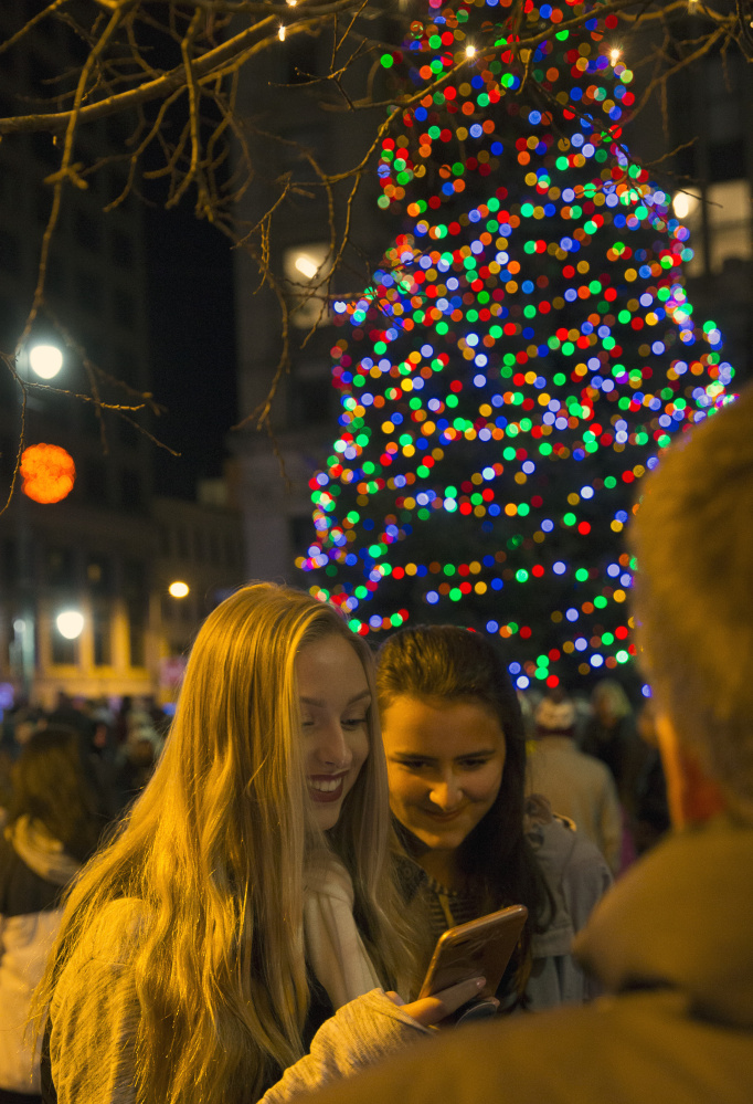 High school friends Kendra Alexander, left, and Courtney Lee check themselves out on Snapchat after the annual tree lighting in Monument Square.