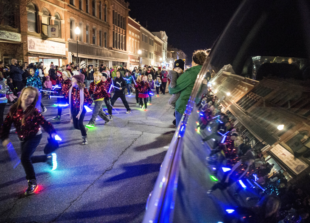 Participants in the annual Parade of Lights march down Main Street on Friday in downtown Waterville.