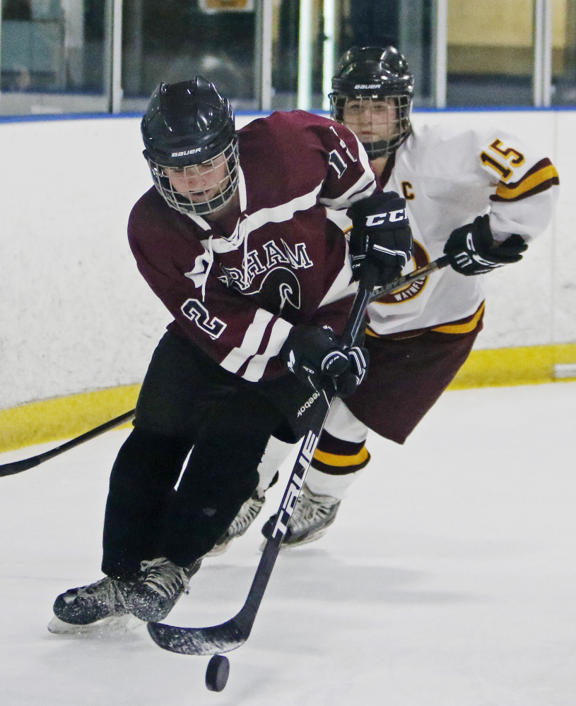 Megan Polchies of Gorham handles the puck behind the net while Erika Miller of Cape Elizabeth pursues during the second period in Portland.