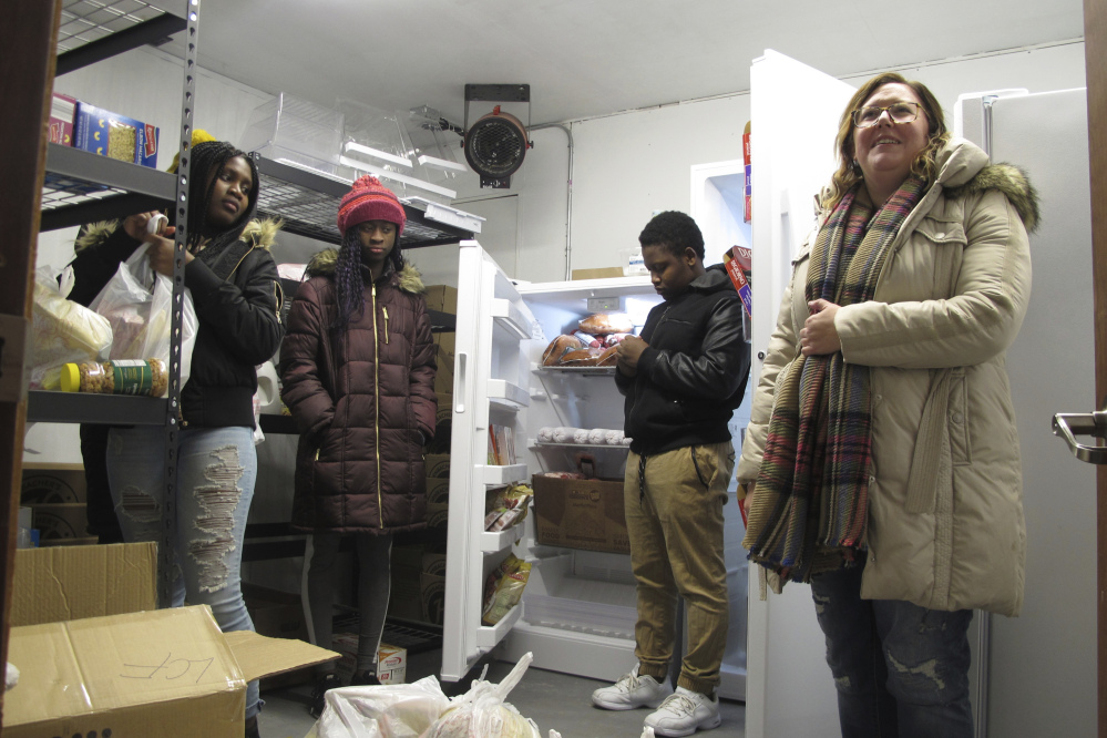 Volunteers at a student-run food pantry, from left, Shinna Sackie, Isa Badje, Joel Gama and Brooke Badjie, help load up bags of groceries on Nov. 16 to be delivered to needy people in Fargo, N.D.
