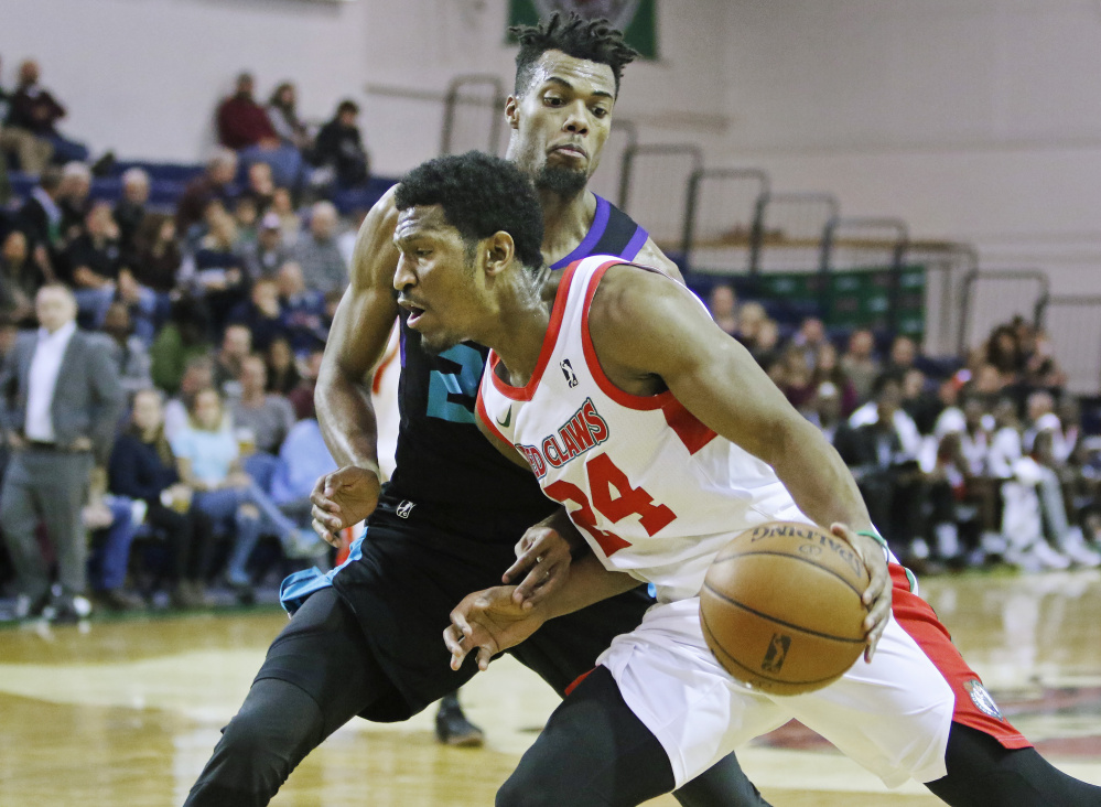 Maine's Andrew White drives around Greensboro's Charles Cooke in third quarter of the Red Claws' 135-111 win Sunday at the Portland Expo.