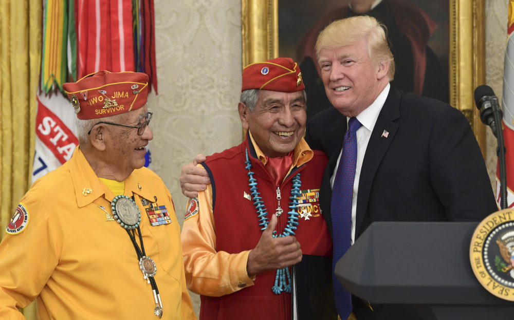 President Trump meets with former Navajo code talkers Peter MacDonald, center, and Thomas Begay, left, in the Oval Office of the White House in Washington on Monday.