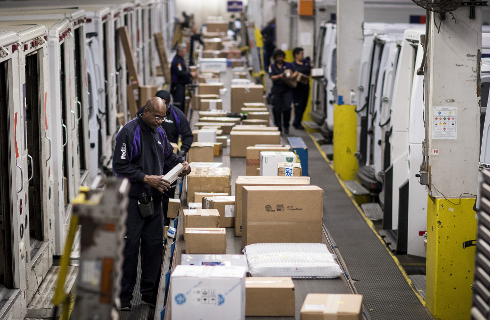 Employees sort packages for delivery at the FedEx Corp. shipping center in Chicago on Monday. C. Britt Beemer of America's Research Group said computers and smaller electronics were the top sellers, followed by clothing.
