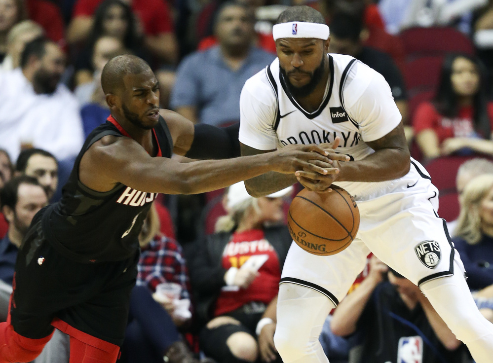 Rockets guard Chris Paul, left, steals the ball from Brooklyn Nets forward Trevor Booker in the first half of Houston's 117-103 win at home Monday night. Paul had 14 assists.