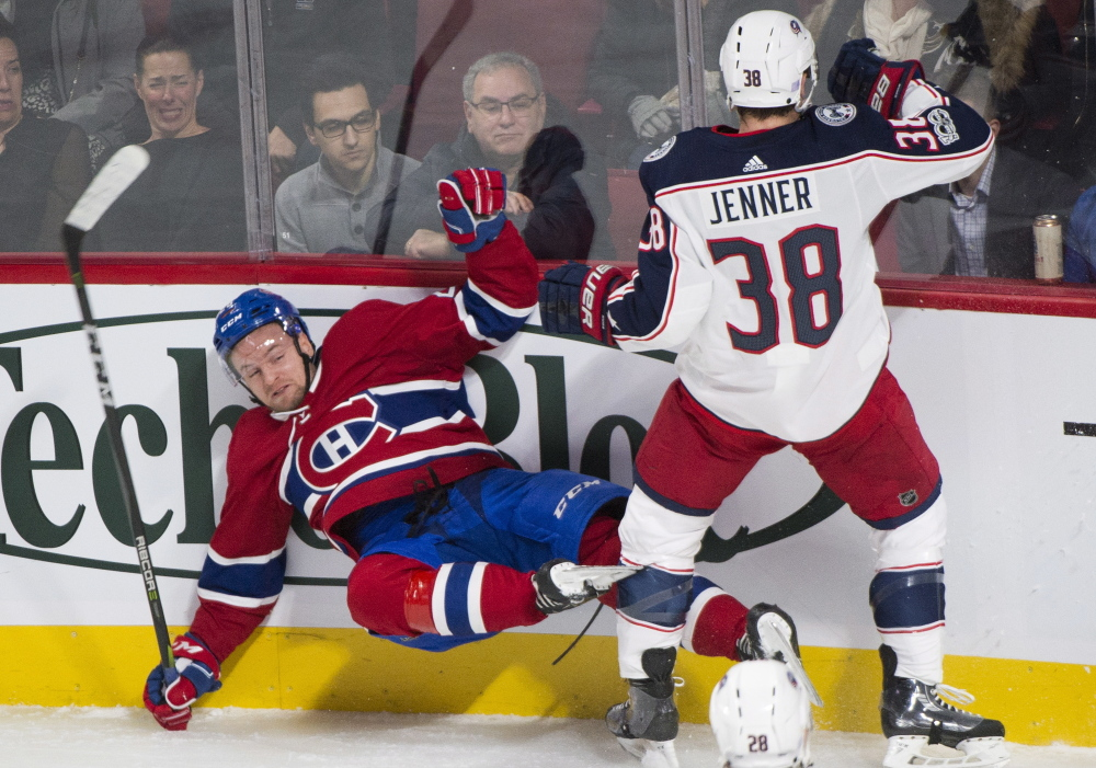 Montreal's Jakub Jerabek is checked into the boards by Columbus' Boone Jenner during first period of the Canadiens' 3-1 win Monday in Montreal.