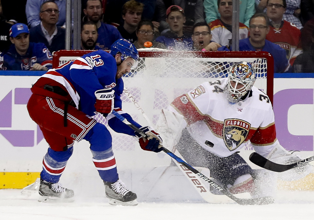 Panthers goalie James Reimer blocks a shot as Kevin Hayes of the Rangers looks for a rebound in the first period Tuesday night in New York. The Panthers scored late in the third period for a 5-4 win.