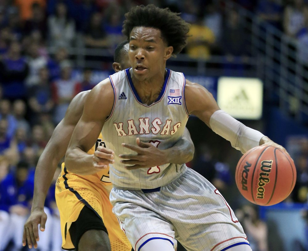 Devonte' Graham of Kansas is hampered by Marreon Jackson of Toledo during the first half Tuesday night. No foul was called on the play. Kansas won, 96-58.