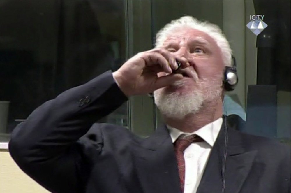 "Slobodan Praljak brings a bottle to his lips during a Yugoslav War Crimes Tribunal in The Hague, Netherlands. Praljak yelled, ""I am not a war criminal!"" and appeared to drink from a small bottle, seconds after judges reconfirmed his 20-year prison sentence for involvement in a campaign to drive Muslims out of a would-be Bosnian Croat ministate in Bosnia in the early 1990s."
