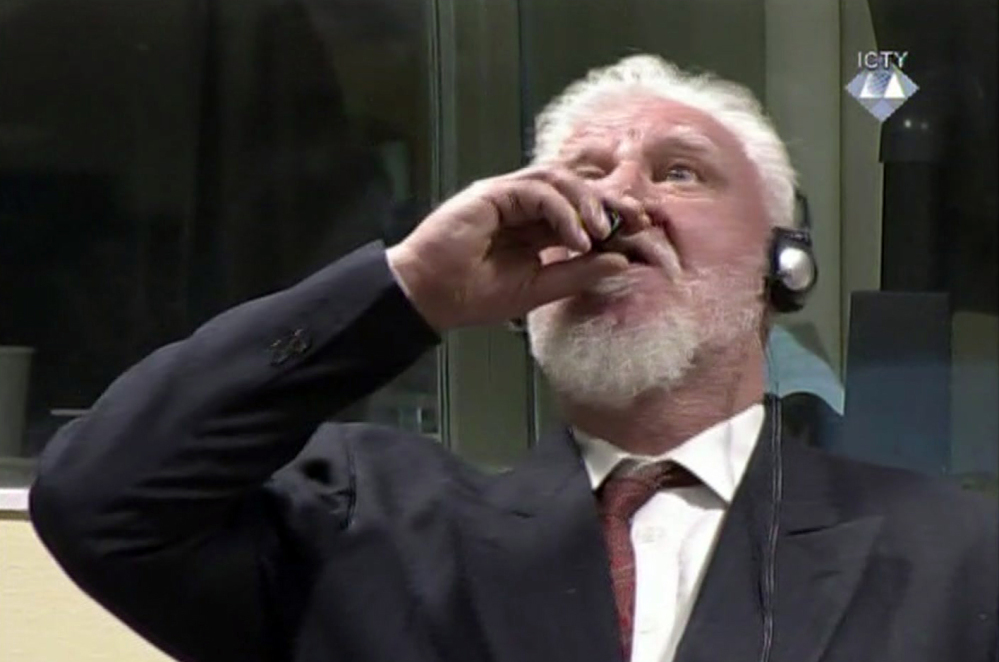 Slobodan Praljak brings a bottle to his lips during a Yugoslav War Crimes Tribunal in The Hague, Netherlands. Praljak yelled,