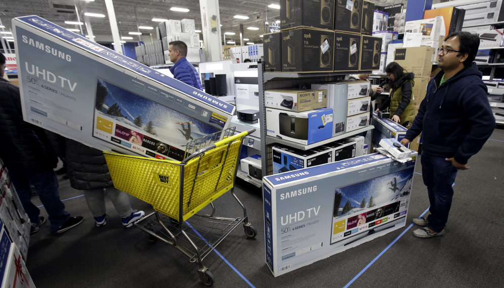People wait to pay for televisions as they shop a sale at a Best Buy store in Overland Park, Kan. For the five-day period that ended Monday, shoppers seemed to spend more in 2017 than a year earlier.