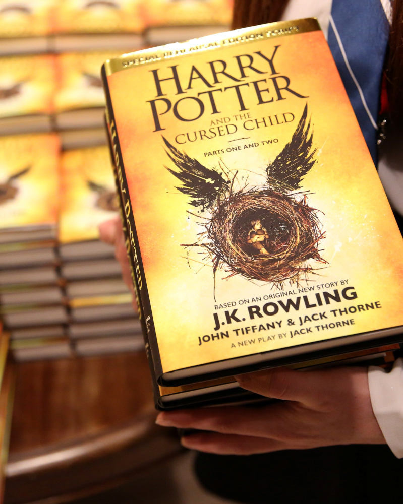 "A store assistant holds copies of the book ""Harry Potter and the Cursed Child"" at a store in London in 2016."