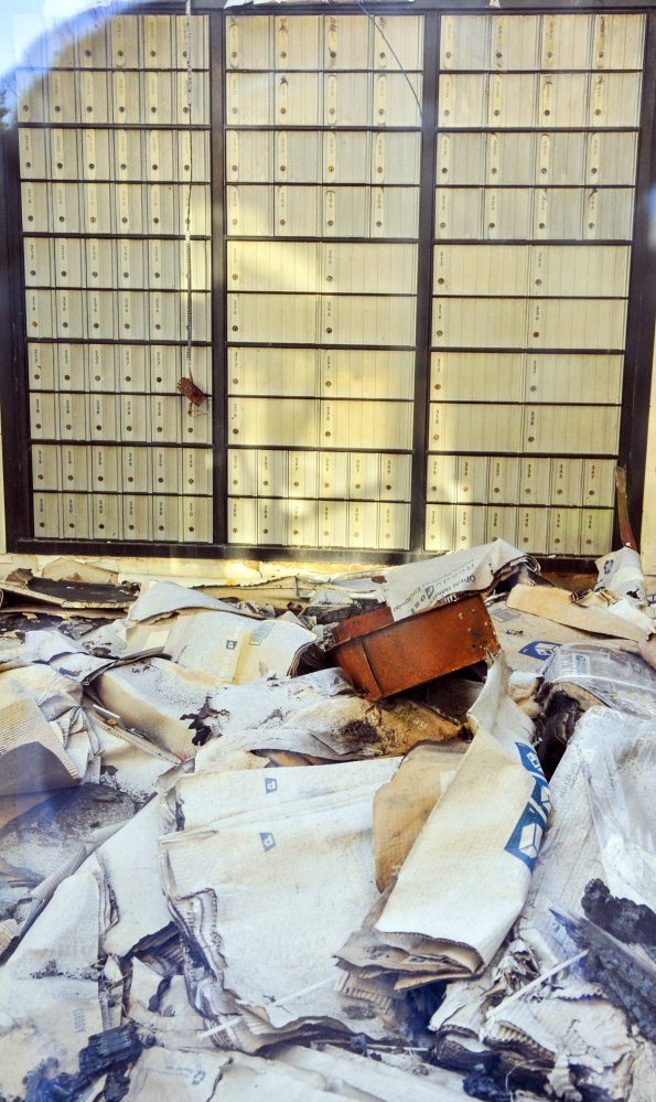 Seen through a window, debris is visible on the lobby floor on Friday inside the burned out U.S. post office in Winthrop.