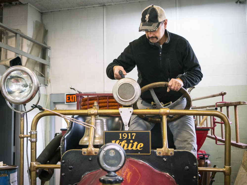 Augusta Fire Chief Roger Audette turns the siren crank on a 1917 White-Kress firetruck.
