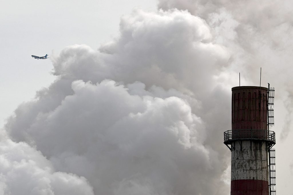 A passenger airplane flies near steam and white smoke emitted from a coal-fired power plant in Beijing. On Monday, scientists projected that global carbon pollution has risen in 2017 after three straight years when the heat-trapping gas didn't go up at all.